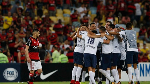 Argentina's Independiente players celebrate clenching the Copa Sudamericana championship title, after tying 1-1 with Brazil's Flamengo at Maracana stadium in Rio de Janeiro, Brazil, Wednesday, Dec.13, 2017. At left is Flamengo's Para. (AP Photo/Leo Correa)