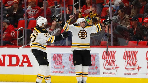 Boston Bruins' Brad Marchand, right, celebrates his goal against the Detroit Red Wings with Patrice Bergeron (37) during overtime of an NHL hockey game Wednesday, Dec. 13, 2017, in Detroit. Boston won 3-2. (AP Photo/Paul Sancya)