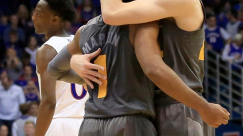 FILE - In this Sunday, Dec. 10, 2017, file photo Arizona State guards Kodi Justice, right, and Remy Martin (1) embrace in the final seconds of an NCAA college basketball game against Kansas in Lawrence, Kan. Arizona State was picked to finish sixth in the Pac-12, its rise expected to come next season, coach Bobby Hurley's fourth in the desert. The breakneck Sun Devils have spun the narrative forward a year early, thrusting themselves into the national spotlight with a road victory over Kansas and a No. 5 ranking.(AP Photo/Orlin Wagner, FIle)