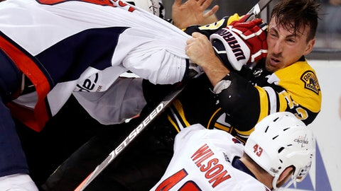 Boston Bruins' Brad Marchand is knocked helmet less to the ice by Washington Capitals' Dmitry Orlov during the second period of an NHL hockey game in Boston Thursday, Dec. 14, 2017. (AP Photo/Winslow Townson)