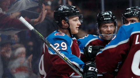 Colorado Avalanche center Nathan MacKinnon, left, is congratulated by defensemen Anton Lindholm, second from left, of Sweden, and Mark Barberio, third from left, as left wing Gabriel Landeskog, front, also of Sweden, joins in the celebration against the Florida Panthers in the third period of an NHL hockey game Thursday, Dec. 14, 2017, in Denver. (AP Photo/David Zalubowski)
