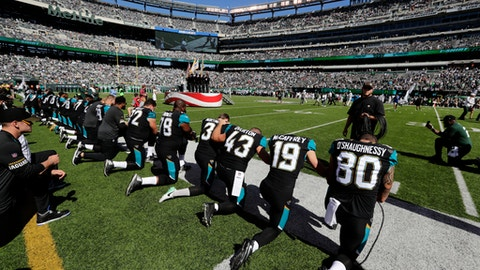 FILE - In this Oct. 1, 2017 file photo, Jacksonville Jaguars players kneel before the national anthem before an NFL football game against the New York Jets in East Rutherford, N.J. The Jacksonville Jaguars says it has no plans to file for Chapter 11 bankruptcy, despite the claims first published in the Patriot Post satire site and shared widely on several conservative sites. The satire piece said the Jaguars had lost income because team members kneeled for the national anthem at home games.  There is no court by that name, and any bankruptcy court filings for Jacksonville would go through the Middle District of Florida.   (AP Photo/Frank Franklin II, File)