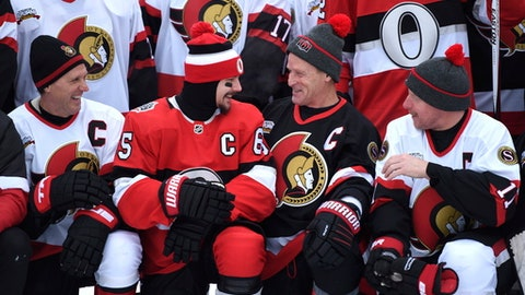 Ottawa Senators captain Erik Karlsson, center left,  laughs with former captain Randy Cunneyworth, center right, as former captains Daniel Alfredsson, right, and Laurie Boschman, left, look on, during a team photo ahead of the NHL 100 Classic hockey match in Ottawa, Friday, Dec. 15, 2017. The Montreal Canadiens will play the Senators on Saturday in the regular season outdoor match. (Justin Tang/The Canadian Press via AP)