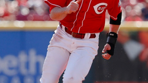 Cincinnati Reds' Zack Cozart runs home to score on an RBI double by Scooter Gennett off Boston Red Sox starting pitcher Doug Fister in the first inning of a baseball game, Sunday, Sept. 24, 2017, in Cincinnati. The Red Sox won 5-4. (AP Photo/John Minchillo)