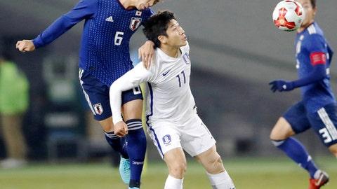 Japan's Genta Miura, left, and South Korea's Lee Keunho vie for the ball at the East Asian Championship in Tokyo, Saturday, Dec. 16, 2017. (Fumine Tsutabayashi/Kyodo News via AP)