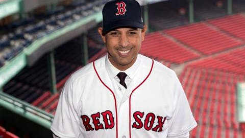 "FILE - In this Nov. 6, 2017, file photo, Boston Red Sox new manager Alex Cora poses in Fenway Park following an introductory news conference in Boston. The Boston Red Sox held a Christmas carnival at Fenway Park on Saturday, Dec. 16, for fans who — like their favorite team — still have some shopping to do. Cora said he wasn't worried about his bosses filling the gap in the lineup. There's no deadline in the offseason,"" Cora said. ""When we get to Feb. 16, we're going to have a good baseball team."" (AP Photo/Michael Dwyer, File)"