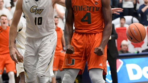 Miami guard Lonnie Walker IV (4) reacts after his dunk next to George Washington forward Patrick Steeves (10) during the second half of an NCAA college basketball game, Saturday, Dec. 16, 2017, in Washington.  . (AP Photo/Nick Wass)