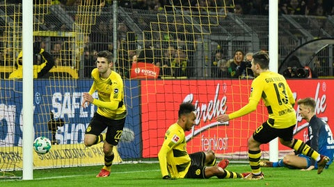 Dortmund's Christian Pulisic, left, scores his side's second goal during the German Bundesliga soccer match between Borussia Dortmund and TSG Hoffenheim in Dortmund, Germany, Saturday, Dec. 16, 2017. (AP Photo/Martin Meissner)