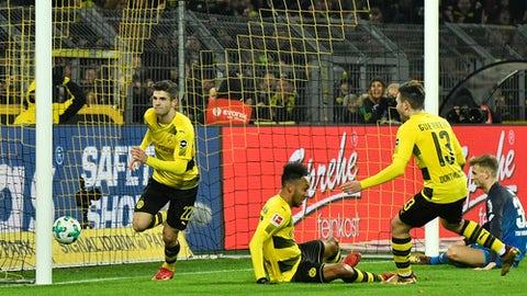 Dortmund's Christian Pulisic, left, scores his side's second goal during the German Bundesliga soccer match between Borussia Dortmund and TSG Hoffenheim in Dortmund, Germany, Saturday, Dec. 16, 2017. (AP Photo/Martin Meissner)