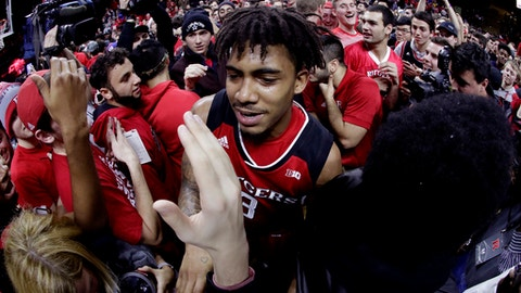 Rutgers guard Corey Sanders, center, is mobbed by fans after Rutgers defeated Seton Hall 71-65 in an NCAA college basketball game, Saturday, Dec. 16, 2017, in Piscataway, N.J. (AP Photo/Julio Cortez)