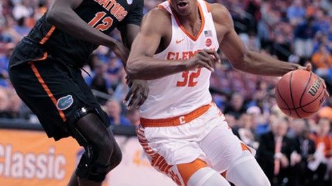 Clemson's Donte Grantham (32) moves the ball on Florida's Gorjok Gak (12) during the first half of an NCAA college basketball game at the Orange Bowl Basketball Classic tournament, Saturday, Dec. 16, 2017, in Sunrise, Fla. (AP Photo/Luis M. Alvarez)