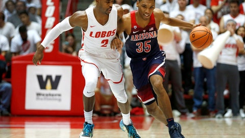 Arizona's Allonzo Trier tries to dribble past New Mexico's Sam Logwood in the first half of an NCAA college basketball game, Saturday, Dec. 16, 2017, in Albuquerque, N.M. (AP Photo/Eric Draper)