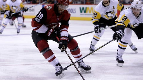 Arizona Coyotes left wing Anthony Duclair (10) skates away from Pittsburgh Penguins defenseman Brian Dumoulin (8) and Kris Letang (58) in the second period during an NHL hockey game, Saturday, Dec 16, 2017, in Glendale, Ariz. (AP Photo/Rick Scuteri)