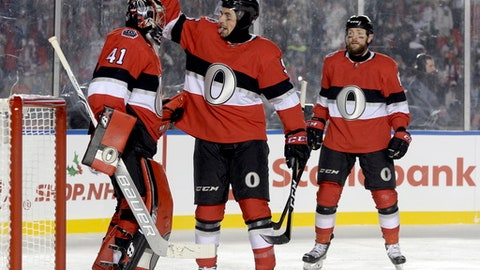 Ottawa Senators defenseman Cody Ceci (5) congratulates goalie Craig Anderson (41) after the final buzzer as Ottawa Senators left wing Zack Smith (15) looks on following third period hockey action against the Montreal Canadiens at the NHL 100 Classic in Ottawa on Saturday, Dec. 16, 2017. (Adrian Wyld/The Canadian Press via AP)