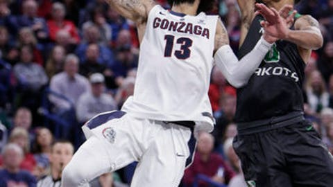 Gonzaga guard Josh Perkins (13) shoots against North Dakota guard Geno Crandall (0) during the second half of an NCAA college basketball game in Spokane, Wash., Saturday, Dec. 16, 2017. (AP Photo/Young Kwak)