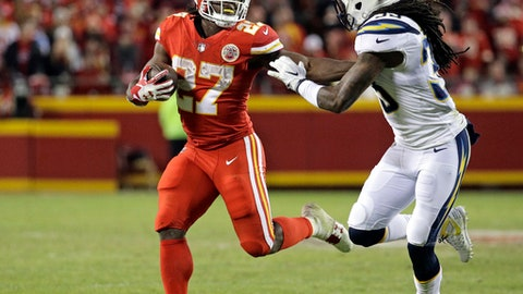 Kansas City Chiefs running back Kareem Hunt (27) is pursued by Los Angeles Chargers safety Tre Boston (33) during the second half of an NFL football game in Kansas City, Mo., Saturday, Dec. 16, 2017. (AP Photo/Charlie Riedel)