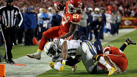 Los Angeles Chargers safety Adrian Phillips (31) tackles Kansas City Chiefs running back Kareem Hunt (27) during the second half of an NFL football game in Kansas City, Mo., Saturday, Dec. 16, 2017. (AP Photo/Charlie Riedel)