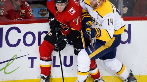 Nashville Predators' Mattias Ekholm, right, of Sweden, checks Calgary Flames' Mark Jankowski during the third period of an NHL hockey game in Calgary, Alberta, Saturday, Dec. 16, 2017. Nashville won, 2-0. (Jeff McIntosh/The Canadian Press via AP)