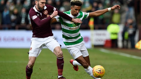 Hearts Michael Smith tackles Celtic's Scott Sinclair during their Scottish Premiership soccer match at Tynecastle Stadium in Edinburgh, Scotland, Sunday Dec. 17, 2017.  Celtic's record 69-match unbeaten run in Scottish soccer ended with a surprise thrashing on Sunday, when they lost 4-0 to Hearts, for its first defeat in any domestic competition since May 2016.(Ian Rutherford/PA via AP)