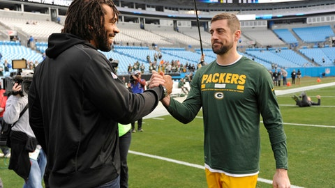 Green Bay Packers' Aaron Rodgers, right, greets former teammate Carolina Panthers' Julius Peppers, left, before an NFL football game in Charlotte, N.C., Sunday, Dec. 17, 2017. (AP Photo/Mike McCarn)