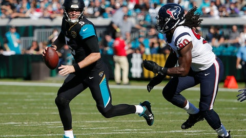 Jacksonville Jaguars quarterback Blake Bortles, left, looks for a receiver as he is pressured by Houston Texans defensive end Jadeveon Clowney (90) during the first half of an NFL football game, Sunday, Dec. 17, 2017, in Jacksonville, Fla. (AP Photo/Stephen B. Morton)