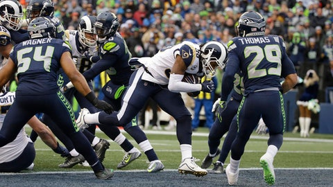 Los Angeles Rams running back Todd Gurley, second from right, rushes for a touchdown as Seattle Seahawks' Bobby Wagner (54) and Earl Thomas (29) look on in the first half of an NFL football game, Sunday, Dec. 17, 2017, in Seattle. (AP Photo/Elaine Thompson)