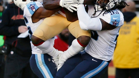 San Francisco 49ers wide receiver Marquise Goodwin, center, makes a catch between Tennessee Titans linebacker Erik Walden, left, and cornerback Adoree' Jackson, right, during the first half of an NFL football game Sunday, Dec. 17, 2017, in Santa Clara, Calif. (AP Photo/D. Ross Cameron)