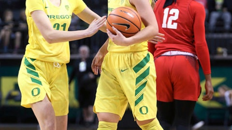 Oregon's Sabrina Ionescu, center, is congratulated by teammate Aina Ayuso, left, after pulling down a rebound to complete her triple-double at end of third quarter to tie an NCAA college basketball record, Sunday Dec. 17, 2017 in Eugene, Ore. She lead her team in scoring as well in a 90-46 win over Mississippi. (Chris Pietsch/The Register-Guard via AP)