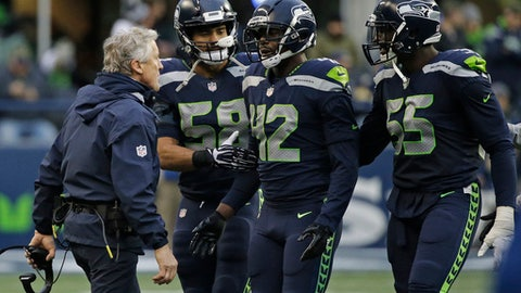 Seattle Seahawks head coach Pete Carroll, left, talks with Seahawks strong safety Delano Hill (42) as Frank Clark, right, and D.J. Alexander, second from left, look on, after Hill was ejected from an NFL football game against the Los Angeles Rams following a scuffle on the field in the second half Sunday, Dec. 17, 2017, in Seattle. (AP Photo/Elaine Thompson)