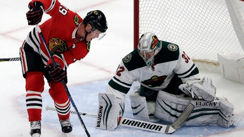 Chicago Blackhawks center Jonathan Toews, left, shoots against Minnesota Wild goalie Alex Stalock during the second period of an NHL hockey game, Sunday, Dec. 17, 2017, in Chicago. (AP Photo/Nam Y. Huh)