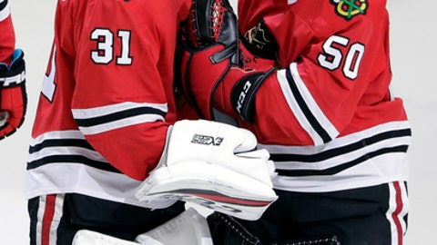 Chicago Blackhawks goalie Corey Crawford, right, celebrates with goalie Anton Forsberg after the Blackhawks defeated the Minnesota Wild 4-1 in an NHL hockey game, Sunday, Dec. 17, 2017, in Chicago. (AP Photo/Nam Y. Huh)