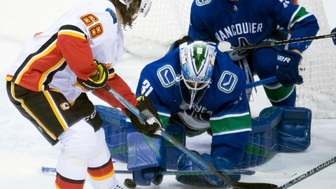 Vancouver Canucks defenseman Troy Stecher (51) looks on as Calgary Flames right wing Jaromir Jagr (68) tries to get a shot past Vancouver Canucks goalie Anders Nilsson (31) during third period NHL hockey action in Vancouver, British Columbia, Sunday, Dec. 17, 2017. (Jonathan Hayward/The Canadian Press via AP)