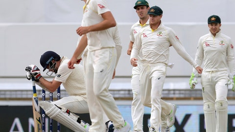 England's James Anderson, left, crouches after he is hit on the helmet by Australia's Pat Cummins during the final day of their Ashes cricket test match in Perth, Australia, Monday, Dec. 18, 2017. (AP Photo/Trevor Collens)
