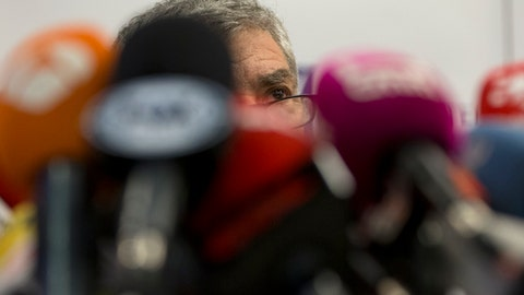 """Former president of Spain's soccer federation Angel Maria Villar speaks behind a bank of microphones during a press conference in Madrid, Spain, Monday, Dec. 18, 2017. The suspended president of the Spanish football federation under investigation for corruption has warned that FIFA could leave Spain out of the World Cup due to alleged meddling by Spain's government in the federation's affairs. Angel Maria Villar said that the """"risk is serious"""" of FIFA suspending the Spanish federation for having removed him from office. Villar and three other soccer officials were arrested in July on suspicion of corruption. (AP Photo/Paul White)"""