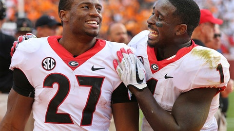 FILE - In this Sept. 30, 2017, file photo, Georgia tailbacks Nick Chubb, left, and Sony Michel celebrate on the sidelines during the fourth quarter of a 41-0 shut out over Tennessee in a NCAA college football game, in Knoxville. It's difficult to imagine Rose Bowl-bound Georgia being one of the final four teams competing for the national championship if not for the decisions by tailbacks Nick Chubb and Sony Michel to return for their senior seasons. The SEC championship and spot in the College Football Playoff is exactly what they hoped to accomplish. B (Curtis Compton/Atlanta Journal-Constitution via AP, File)