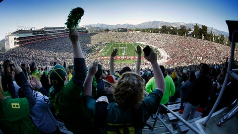 FILE - In this Jan. 1, 2015, file photo, Oregon fans cheer as their team takes to the field before the Rose Bowl NCAA college football playoff semifinal, in Pasadena, Calif. Group of Five teams will mostly play in third-tier bowl games in front of sparse crowds, earning payouts that mostly cover travel expenses. The Power Five teams get the glamor bowls with the multimillion-dollar payouts. (AP Photo/Richard Vogel, File)