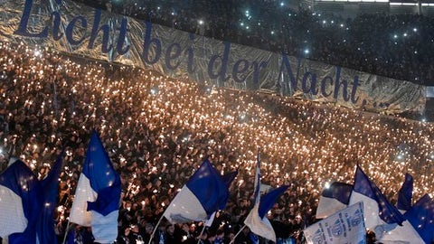 Thousands of Schalke supporters hold little sparkler prior the German soccer cup match between FC Schalke 04 and 1. FC Cologne in Gelsenkirchen, Germany, Tuesday, Dec. 19, 2017. (AP Photo/Martin Meissner)