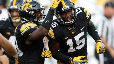 """FILE - In this Sept. 16, 2017, file photo, Iowa's Josh Jackson (15) celebrates with teammate Miles Taylor, left, after intercepting a pass during the second half of an NCAA college football game against North Texas, in Iowa City, Iowa. Next week's Pinstripe Bowl in New York could be Iowa junior cornerback Josh Jackson's last game as a Hawkeye.  Jackson said Tuesday, Dec. 19. 2017, that he's """"50-50"""" on whether he'll come back for his senior season, adding that he'll likely announce his plans for 2018 after the Hawkeyes (7-5) face Boston College (7-5) on Dec. 27 at Yankee Stadium.  (AP Photo/Charlie Neibergall, File)"""