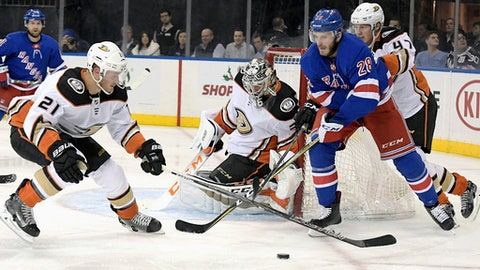 Anaheim Ducks goalie John Gibson (36) deflects the puck as New York Rangers center Paul Carey (28) and Ducks center Chris Wagner (21) looks to control it during the second period of an NHL hockey game, Tuesday, Dec.19, 2017, at Madison Square Garden in New York. (AP Photo/Bill Kostroun)