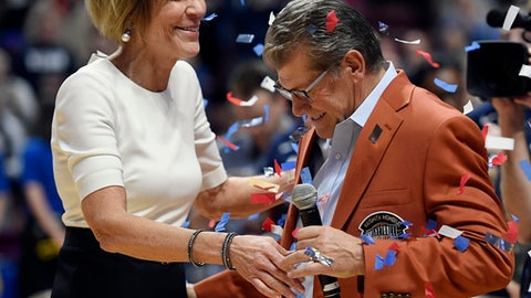 Connecticut associate head coach Chris Dailey, left, and head coach Geno Auriemma celebrate Auriemma's 1000th win at the end of an NCAA college basketball game against Oklahoma, Tuesday, Dec. 19, 2017, in Uncasville, Conn. (AP Photo/Jessica Hill)