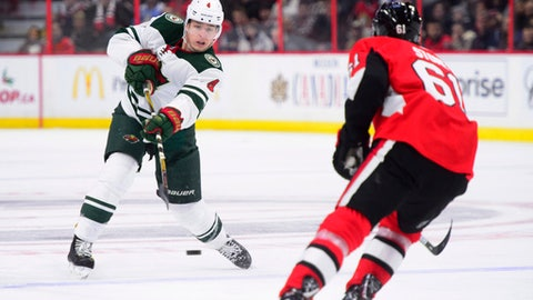 Minnesota Wild's Mike Reilly dumps the puck past Ottawa Senators' Mark Stone during third period NHL hockey action in Ottawa on Tuesday, Dec. 19, 2017. (Sean Kilpatrick/The Canadian Press via AP)