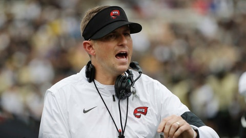 FILE - In this Nov. 4, 2017, file photo, Western Kentucky head coach Mike Sanford watches the action in the first half of an NCAA college football game against Vanderbilt, in Nashville, Tenn. When Alabama switched offensive coordinators during last season's playoff, it had an in-house solution. The Crimson Tide's support staff included former Washington and Southern California head coach Steve Sarkisian, who took over the offense for the championship game. Western Kentucky didn't have that luxury this season when offensive line coach Geoff Dart was diagnosed with brain tumors and underwent surgery to limit his availability. The Hilltoppers had to rely on tight ends coach Mike Mahaffey and graduate assistant Mike Bivin to pick up the slack. Those two examples underscore the difference in staff sizes between Power Five programs and Group of Five schools. (AP Photo/Mark Humphrey, File)