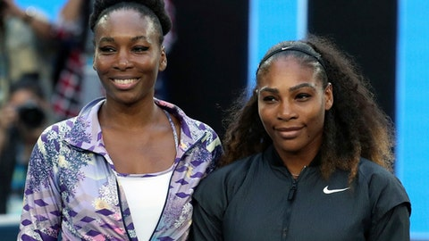 FILE - In this Jan. 28, 2017, file photo, Venus, left, and Serena Williams pose ahead of the women's singles final at the Australian Open tennis championships in Melbourne, Australia. While the Miami Open is giving up its picturesque island setting for suburban sprawl, the tennis tournament's new home will include a 13,800-seat showcase court in the Miami Dolphins' stadium and 29 permanent outer courts, with the largest seating 5,042 spectators. Venus and Serena Williams have small ownership stakes in the Dolphins. (AP Photo/Aaron Favila, File)