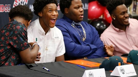 From left, Miami Southridge High football players attend a press conference after signing to play NCAA college football in Miami, Wednesday, Dec. 20, 2017. From left are Mark Pope, Daquris Wiggins, and Delone Scaife, who all signed with the University of Miami, and James Head, far right, who signed with Indiana University. (Carl Juste/Miami Herald via AP)