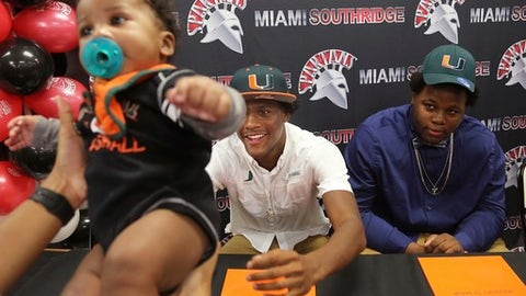 Daquris Wiggins reaches out for his 4 month-old cousin, Sidney August, as teammate Delone Scaife, looks on after the teammates signed with the University of Miami NCAA college football team in Miami, Wednesday, Dec. 20, 2017.  (Carl Juste/Miami Herald via AP)