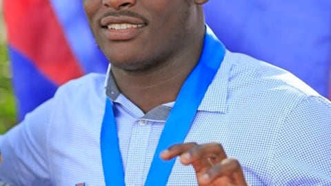 Donovan Georges, a Champagnat Catholic High School football player, gestures as he announces his intentions to attend Florida International University during the NCAA college football early signing period, Wednesday, Dec. 20, 2017, in Sunrise, Fla. (Al Diaz/Miami Herald via AP)