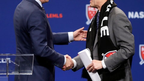 Major League Soccer commissioner Don Garber, left, shakes hands with John Ingram, chairman of Ingram Industries Inc., after Garber announced that Nashville, Tenn. has been awarded a Major League Soccer franchise Wednesday, Dec. 20, 2017, in Nashville, Tenn. Ingram is the head of the group seeking to bring the team to Nashville. (AP Photo/Mark Humphrey)