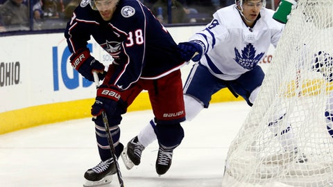 Toronto Maple Leafs defenseman Connor Carrick, right, tries to stop Columbus Blue Jackets forward Boone Jenner during the second of an NHL hockey game in Columbus, Ohio, Wednesday, Dec. 20, 2017. (AP Photo/Paul Vernon)