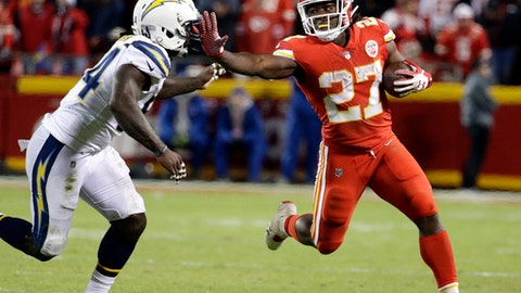 FILE - In this Dec. 16, 2017, file photo, Kansas City Chiefs running back Kareem Hunt (27) runs away from Los Angeles Chargers linebacker Melvin Ingram (54) during the second half of an NFL football game in Kansas City, Mo. The Chiefs head into their regular-season home finale against the Miami Dolphins on Sunday with a playoff situation that is straightforward and favorable. They're the AFC West champs if they win. Or if the Chargers lose to the Jets. Hunt has run for 1,201 yards, trailing Steelers star Le'Veon Bell by 21 yards for the league lead. (AP Photo/Charlie Riedel, File)