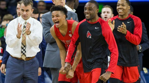 FILE - In this Dec. 5, 2017, file photo, Ball State players and head coach James Whitford, left, celebrate after going on a run during the second half of an NCAA college basketball game against Notre Dame, in South Bend, Ind. This season was supposed to be different. Players talked openly about a third straight 20-win season, pursuing their first league title in 18 seasons, celebrating their first NCAA tourney win since 1990 and, yes, even adding a banner or two to the dusty collection. Everything changed for the Cardinals when 19-year-old 6-foot-9 forward Zach Hollywood was found dead in his apartment after committing suicide. Players wear a patch bearing Hollywood's initials just above their hearts. (AP Photo/Robert Franklin, File)